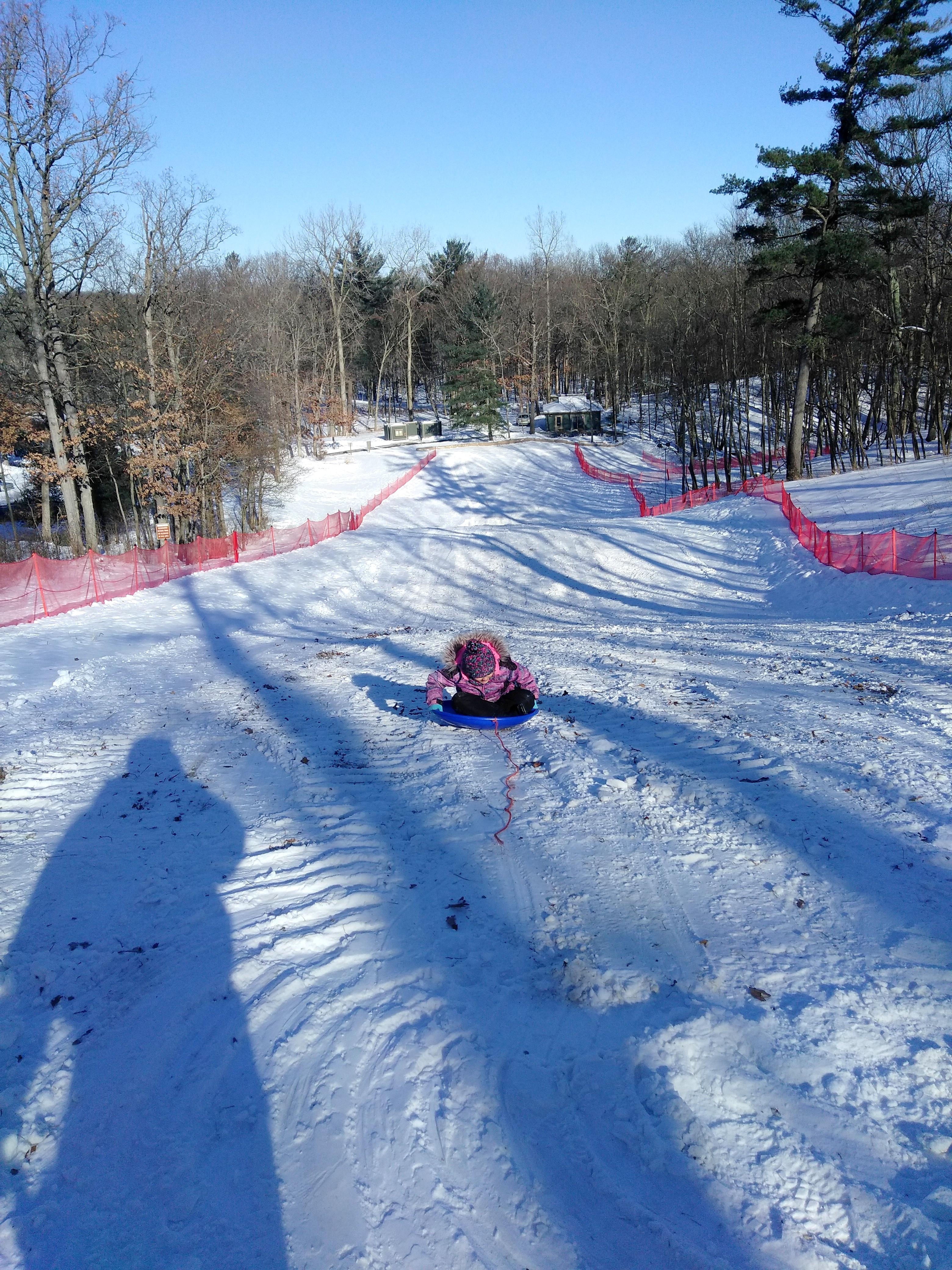 Abby sledding backward on big hill at Lost Lake